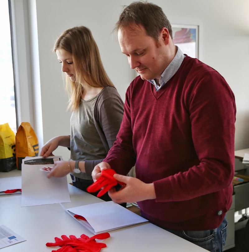 Zwei Mitarbeiter bereiten Red Hand Day vor