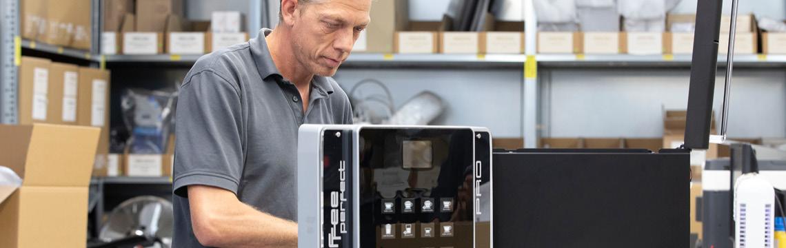En mand reparerer en fuldautomatiske kaffemaskine